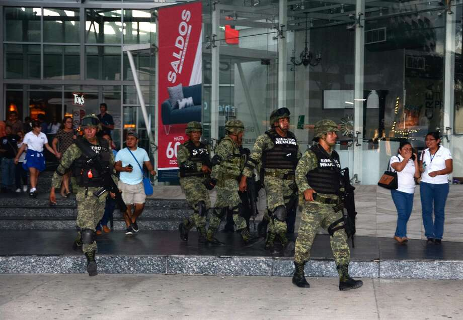 Mexican soldiers evacuate civilians from a shopping center in the vicinity of the place where a shooting erupted ensuing an attack against the building of the Quintana Roo State Prosecution, in Cancun, Mexico, on January 17, 2017.  The shooting happened as Mexican authorities investigate whether a feud over local drug sales was behind a nightclub shooting that killed three foreigners and two Mexicans Monday at the Blue Parrot club during the BPM electronic music festival in Playa del Carmen, a usually peaceful Caribbean seaside town. / AFP / STR Photo: STR/AFP/Getty Images