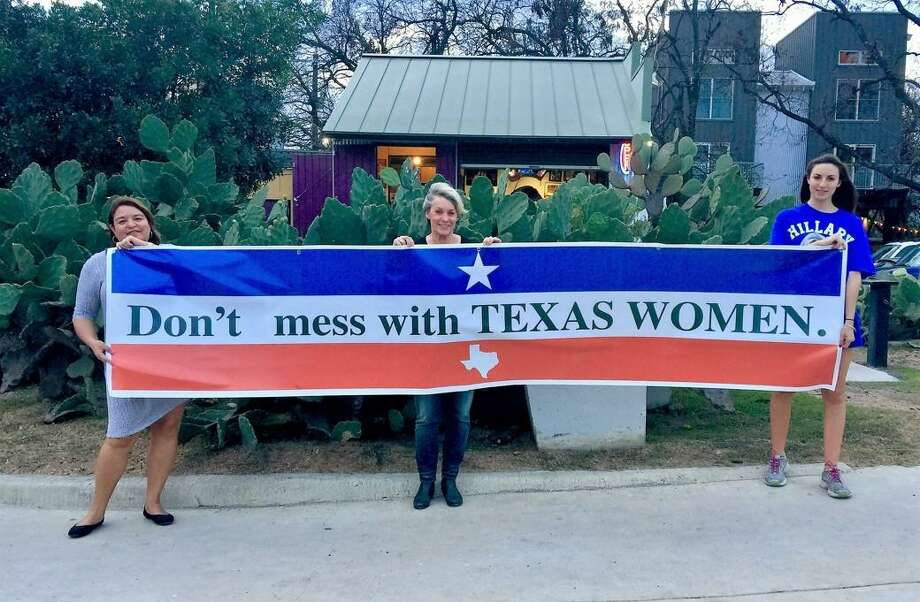 Joined by Kathy Coiner, left, and her daughterRuby Martinez-Berrier, right, Suzanne Martinez of San Antonio, center, holds a banner she will carry at the Women's March on Washington. Martinez plans to attend the march with her daughter. Photo: Suzanne Martinez / Courtesy Photo