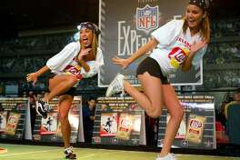 Brittany Villareal (L) and Julie Zell of Cypress Texas compete in the Lays' Touchdown Dance Contest at the NFL Experince on January 23, 2004 at the George R. Brown Convention Center.