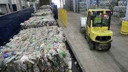 Recycled plastic bottles sit on a conveyor belt to be processed at the Repreve Bottle Processing Center, part of the Unifi textile company in Reidsville, N.C. U.S. industrial production increased in December at the strongest pace in two years.
