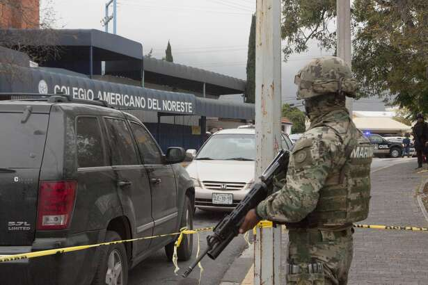 A marine stands guard outside a high school where a student opened fire on his classmates in Monterrey, Mexico, on January 18, 2017. A high school student shot his teammates at a college in Monterrey, an industrial city in northeastern Mexico, in an unprecedented event that left five people injured, including the assailant who attempted suicide, authorities in the state of Nuevo Leon reported. / AFP / Julio Cesar AGUILAR        (Photo credit should read JULIO CESAR AGUILAR/AFP/Getty Images)