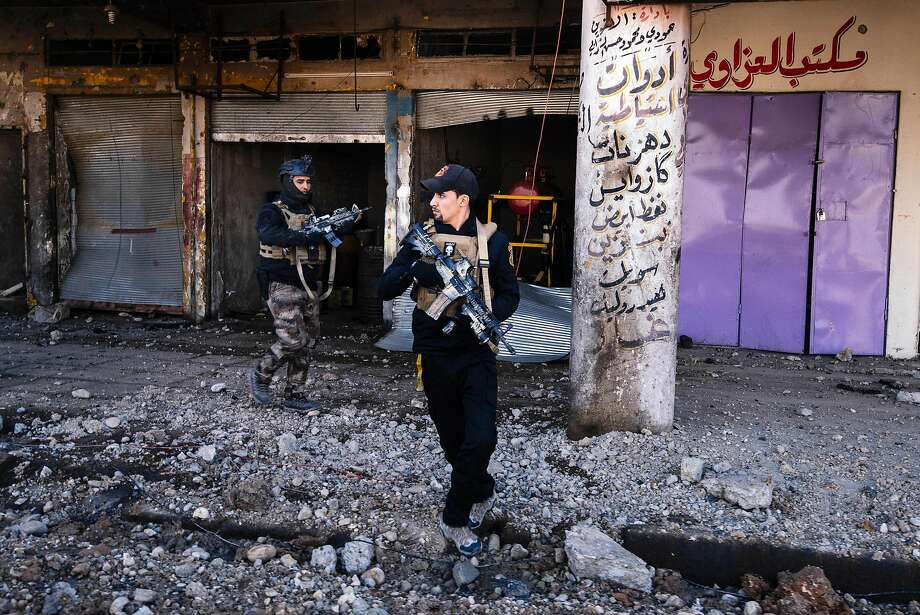 Iraqi special forces patrol next to destroyed shops in eastern Mosul after battling Islamic State fighters. Photo: DIMITAR DILKOFF, AFP/Getty Images