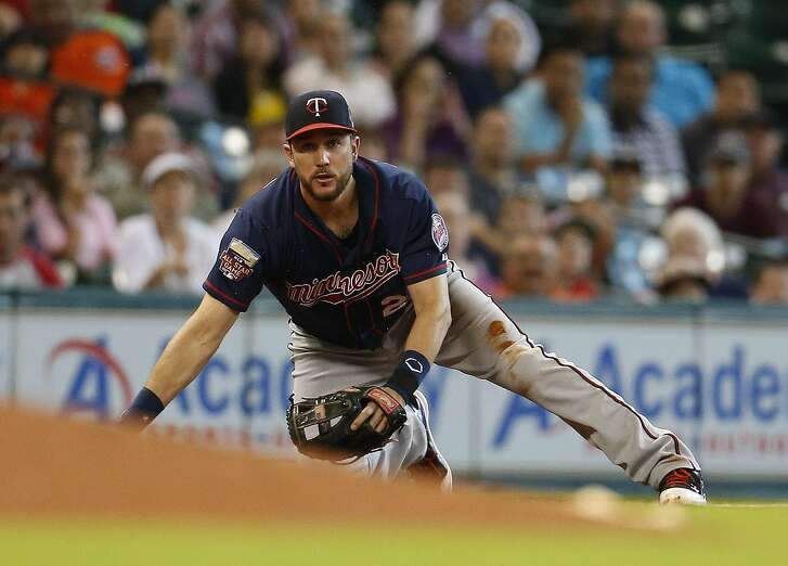 Minnesota Twins third baseman Trevor Plouffe (24) watches his throw to first from his knees on a challenged ground out hit by Houston Astros second baseman Jose Altuve during the third inning of an MLB baseball game at Minute Maid Park, Wednesday, Aug. 13, 2014, in Houston.  ( Karen Warren / Houston Chronicle  )