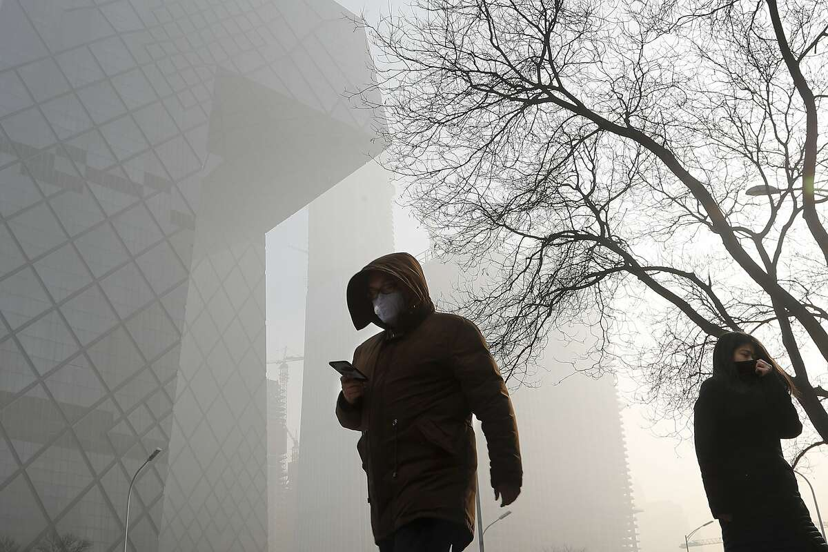 People wearing protection masks walk near the iconic headquarters of China's state broadcaster Central China Television (CCTV) at the Central Business District in Beijing as the capital of China is blanked by heavy smog on Tuesday, Jan. 3, 2017. China's Ministry of Environment says an unspecified number of companies have violated measures meant to reduce smog as the country deals with a phase of particularly noxious pollution. Beijing has been on