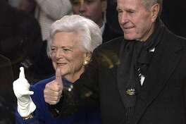 Former President George H.W. Bush (R) and former First Lady Barbara Bush give the thumbs-up from inside the presidential viewing stand overlooking Pennsylania Avenue during the Inaugural Parade 20 January 2005 in Washington, DC. In the 55th US presidential inauguration and the first since the September 11, 2001 attacks, Bush solemnly took the oath of office and declared that defeating terrorism required embracing a global mission to foment democracy. AFP PHOTO STAN HONDA        (Photo credit should read STAN HONDA/AFP/Getty Images)