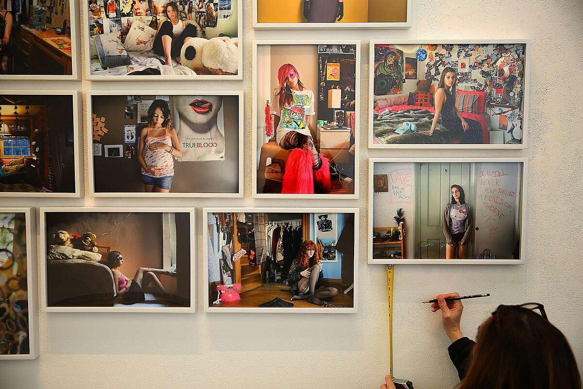 """Gallery director Ann Jastrab installs portraits from photographer Rania Matar featuring works from """"A Girl and Her Room, """"L'Enfant-Femme"""", and """"Unsopoken Conversations"""" at RayKo Photo Center on Tuesday, January 17, 2017, in San Francisco, Calif."""