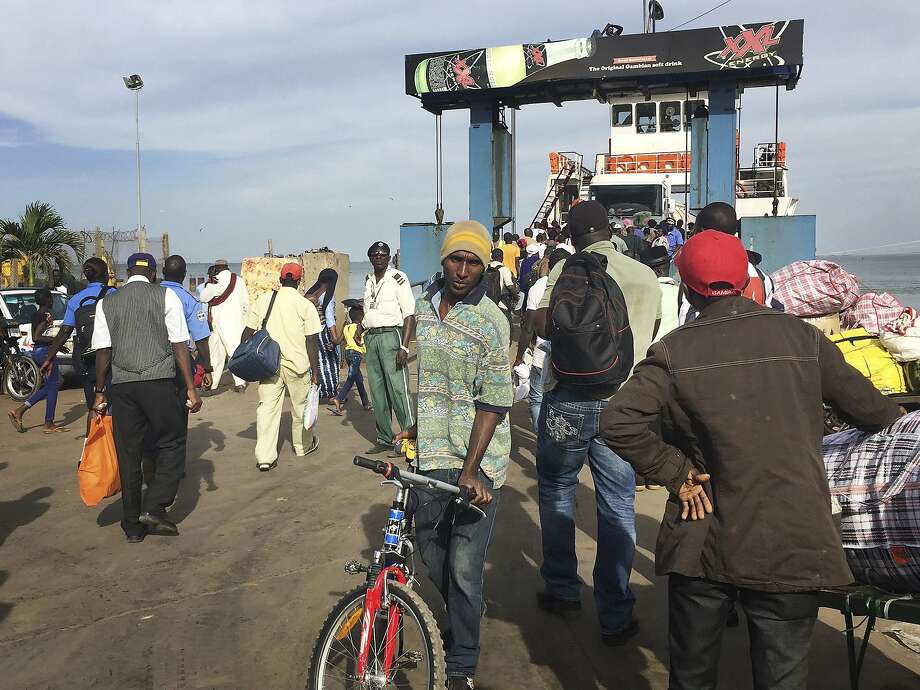 Residents fleeing the capital, Banjul, board a ferry boat. Hundreds of foreign tourists have evacuated the city on special charter flights ahead of a possible regional military intervention. Photo: Associated Press