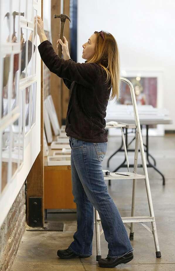 RayKo gallery director Ann Jastrab installs portraits from Rania Matar. Photo: Liz Hafalia, The Chronicle