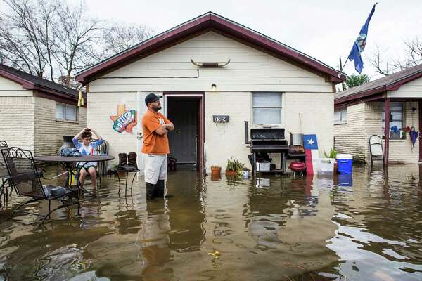 Carlos Gutierrez stands in water from heavy overnight rains surrounding his house near the 2600 block of Creston on Wednesday, Jan. 18, 2017, in Houston.