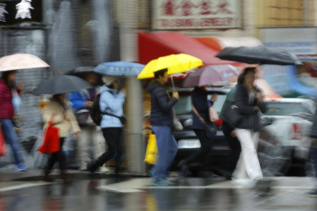 People under umbrellas cross the street under rainy skies at the corner of Jackson and Stockton streets in Chinatown, in San Francisco, Ca., on Wednesday Jan. 18, 2017, as the first of a series of storms roll across the Bay Area.