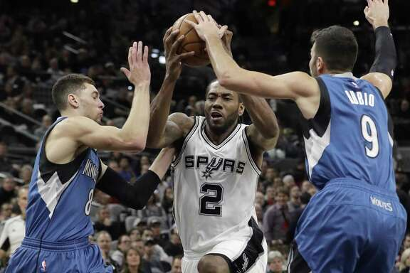 Spurs forward Kawhi Leonard drives to the basket between Minnesota Timberwolves defenders Zach LaVine (8) and Ricky Rubio (9) during the second half on Jan. 17, 2017, in San Antonio. The Spurs won 122-114.