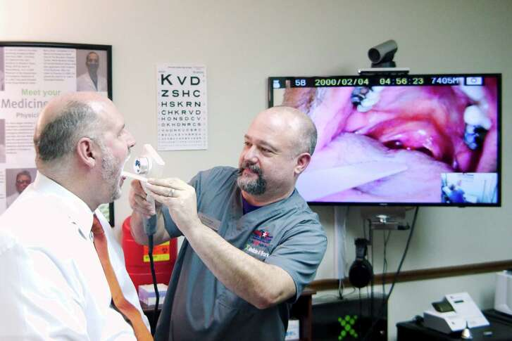 Paramedic Rob Koonce performs a throat examination on Nu Physicia CEO Dr. Glenn Hammock to demonstrate how medical care is administered at the new telemedicine clinic for Deer Park city employees. The clinic at 203 Ivy Ave. Suite 206 is operated by Hammock's company.