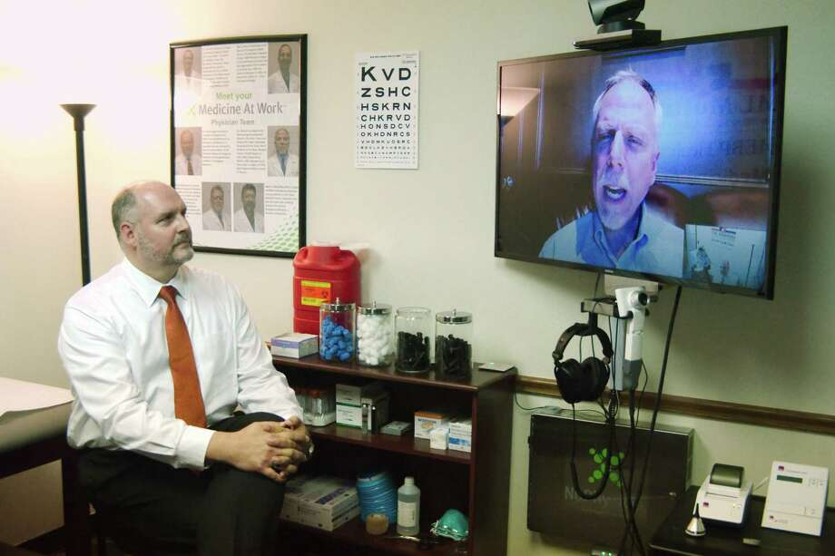 Nu Physicia CEO Dr. Glenn Hammock chats with Dr. Mark Ahearn via video conference at the telemedicine clinic for city of Deer Park employees. Photo: Kirk Sides / © 2016 Kirk Sides / Houston Community Newspapers