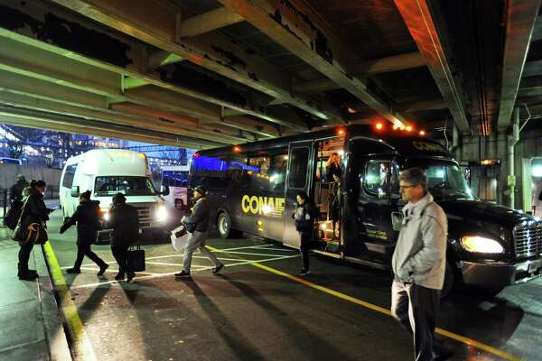 Passengers disembark private shuttles at the Stamford Transportation Center on Jan. 11. These private shuttles take employees directly from their place of employment to the train station daily.