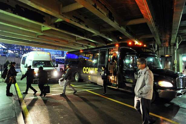 Passengers disembark private shuttles at the Stamford Transportation Center in Stamford, Conn. on Wednesday, Jan. 11, 2017. These private shuttles take employees directly from their place of employment to the train station daily.