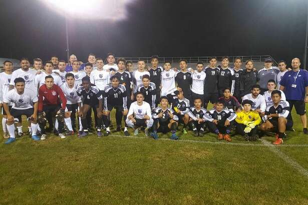 Current and former varsity soccer players pose for a picture after the game