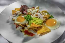 Chilaquiles (Hugo's totopos bathed in tomatillo salsa with chicken and topped with two eggs sunny-side-up) at Hugo's