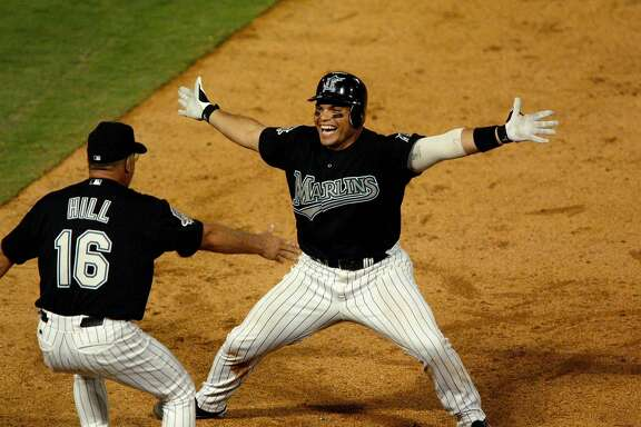 Florida Marlins' Ivan Rodriguez, right, celebrates with first base coach Perry Hill after hitting the game-winning single in the 11th inning against the San Francisco Giants on Friday, Oct. 3, 2003, in Miami. The Marlins won, 4-3, putting them ahead in the 2-1 in the best-of-five series. (AP Photo/Palm Beach Post, Gary Coronado)  HOUCHRON CAPTION  (10/04/2003):  Florida's Ivan Rodriguez is ready to celebrate with first base coach Perry Hill after his 11th inning single won Friday's game.