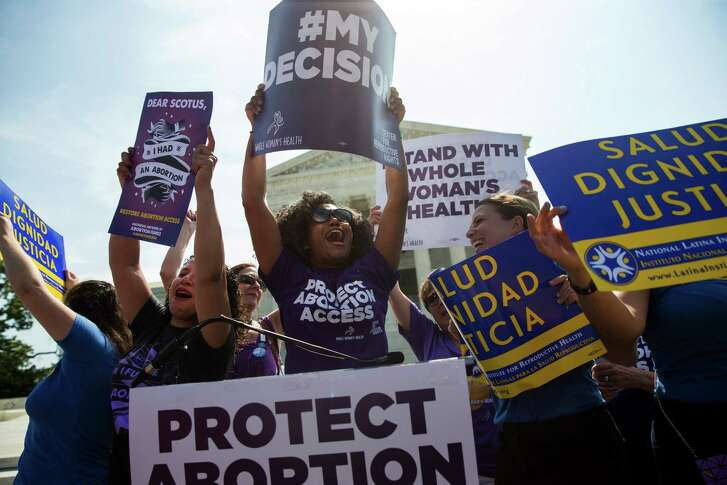Pro-abortion rights activists celebrate during a rally in Washington, D.C. Tens of thousands of women expected for a march Saturday come packing a multitude of agendas, but are united in their loathing for Donald Trump.