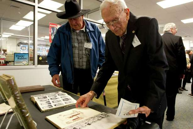 Herbert Lamp, a 1943 graduate from Davy Crocket High School, looks over high school yearbooks alongside Shelby Ralston, graduate 1960, during a celebration for Travis Intermediate School's 90th birthday Wednesday, Jan. 18, 2017, in Conroe. The school has served various education roles for Conroe ISD in its 90-year history, including time as a junior high school, high school, and alternative school.