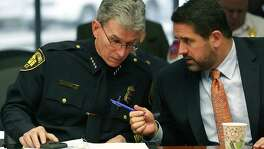 San Antonio Police Chief William McManus, left, listens to Deputy City Manager Erik Walsh before McManus addressed the City Council's Criminal Justice, Public Safety and Services subcommittee about last year's uptick in violent crime, in the municipal Plaza B on Wednesday. The homicide rate went down, however.