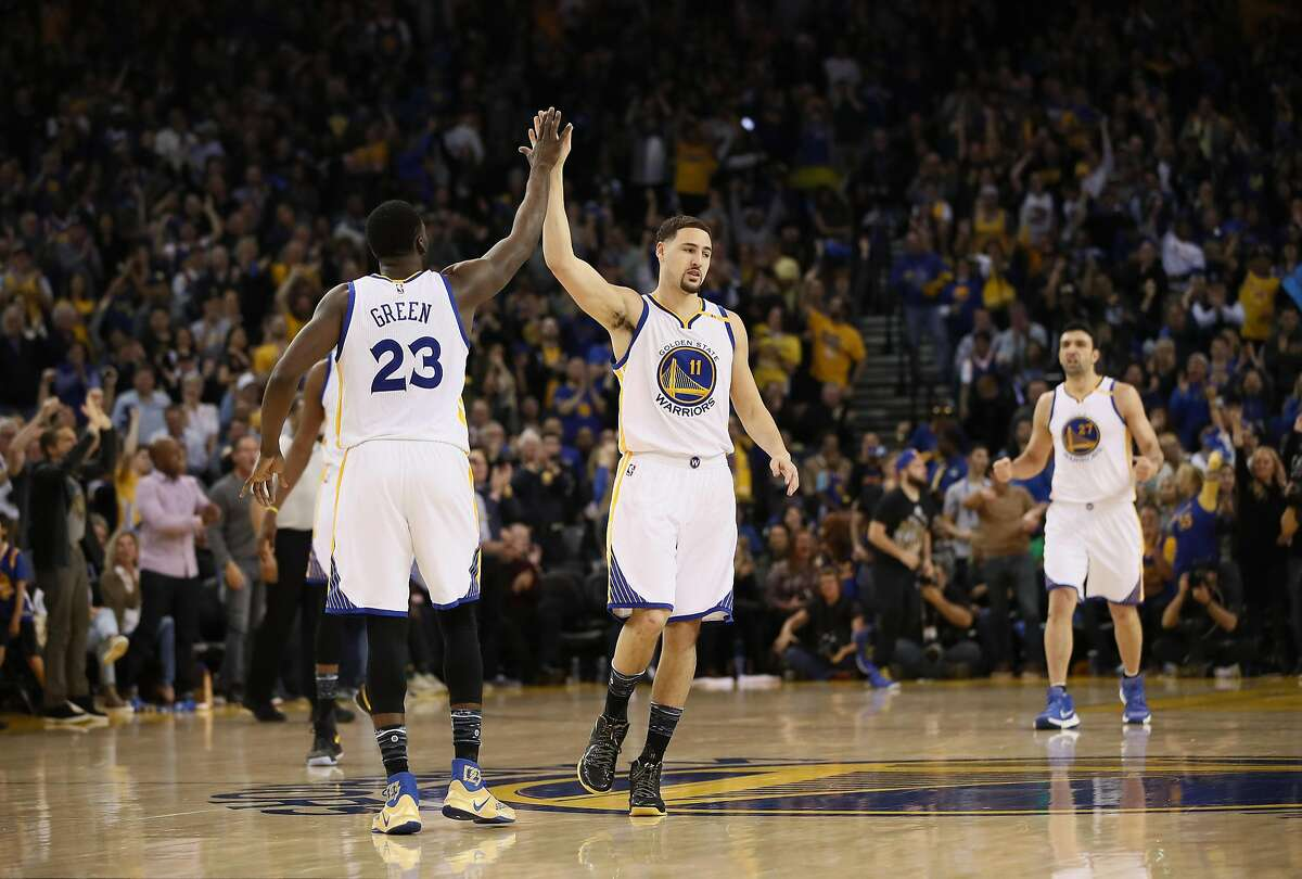 OAKLAND, CA - JANUARY 16: Draymond Green #23 high fives Klay Thompson #11 of the Golden State Warriors during their game against the Cleveland Cavaliers at ORACLE Arena on January 16, 2017 in Oakland, California. NOTE TO USER: User expressly acknowledges and agrees that, by downloading and or using this photograph, User is consenting to the terms and conditions of the Getty Images License Agreement. (Photo by Ezra Shaw/Getty Images)