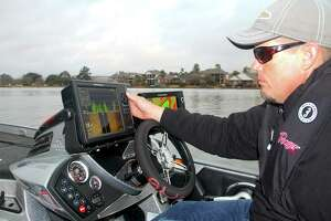 Professional bass tournament angler Keith Combs uses some of his boat's extensive marine electronics to help locate potential fishing areas while scouting Lake Conroe, site of the Bassmaster Classic. He's one of five Texans in the event.