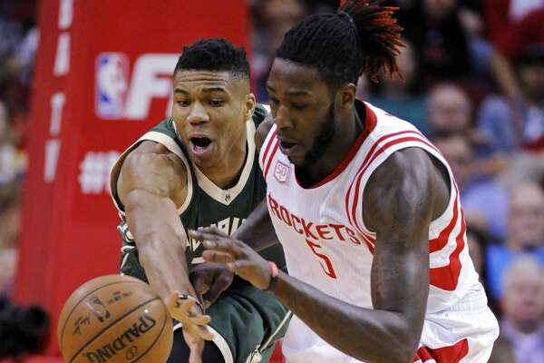 Milwaukee Bucks forward Giannis Antetokounmpo, left, and Houston Rockets forward Montrezl Harrell fight for a loose ball during the first half of an NBA basketball game, Wednesday, Jan. 18, 2017, in Houston. (AP Photo/Eric Christian Smith)