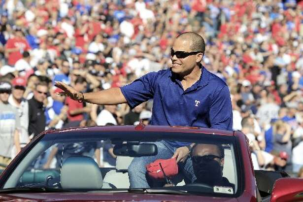 Former Texas Rangers catcher Ivan Rodriguez rides into the stadium and waves to fans before the baseball game between the New York Yankees and the Rangers on Monday, April 23, 2012, in Arlington, Texas.  (AP Photo/LM Otero)