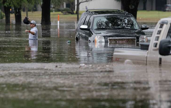 A man makes his way through waist-high waters after being forced to abandon his flooded SUV after getting stranded along Stancliff near U.S. 59 and West Bellfort on Wednesday.