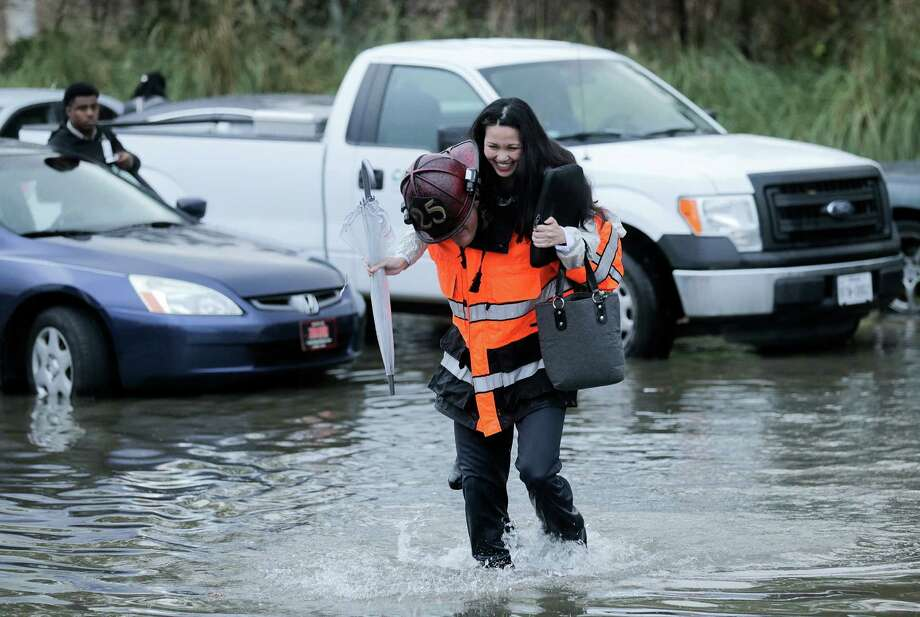 A motorist gets a lift from a Houston firefighter after leaving her car on flooded Highway 288. Photo: Elizabeth Conley, Staff / © 2017 Houston Chronicle
