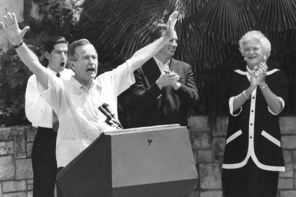 Vice President and presidential candidate George H.W. Bush acknowledges the crowd as Roy Barrera Jr., Tom Loeffler and wife Barbara Bush applaud during a rally at Arneson River Theater on Aug. 25, 1988. San Antonio Express-News file photo
