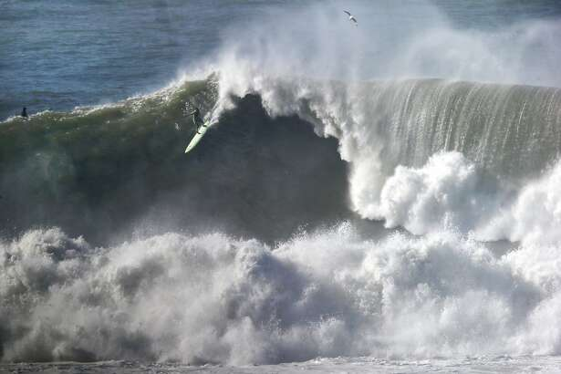 A surfer takes off on a large wave at Maverick's in Half Moon Bay, CA Wednesday, January 7, 2016.