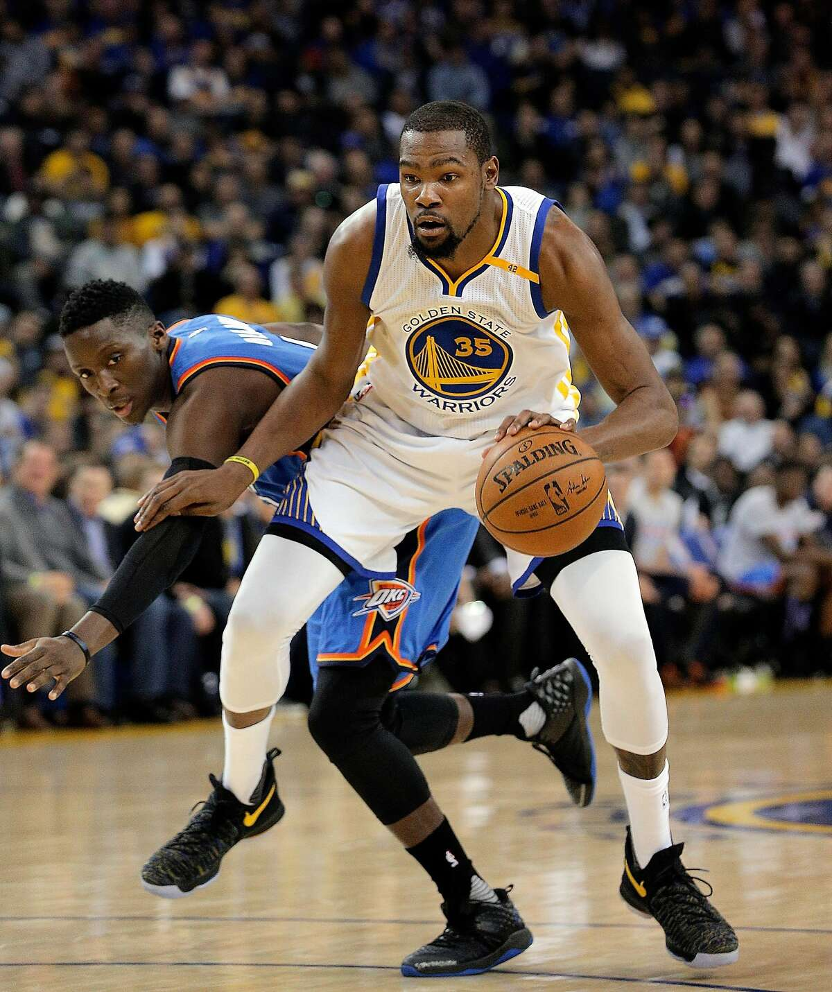 Kevin Durant (35) drives to the basket defended by Victor Oladipo (5) as the Golden State Warriors played the Oklahoma City Thunder at Oracle Arena in Oakland, Calif., on Wednesday, January 18, 2017.
