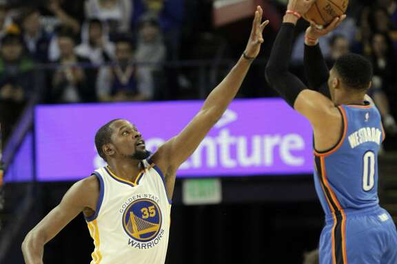 Kevin Durant (35) tries to block a shot by Russell Westbrook (0) as the Golden State Warriors played the Oklahoma City Thunder at Oracle Arena in Oakland, Calif., on Wednesday, January 18, 2017.