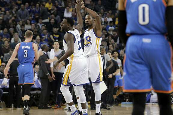 Draymond Green (23) high fives Kevin Durant (35) after Durant hit a three pointer in the second half as the Golden State Warriors played the Oklahoma City Thunder at Oracle Arena in Oakland, Calif., on Wednesday, January 18, 2017.
