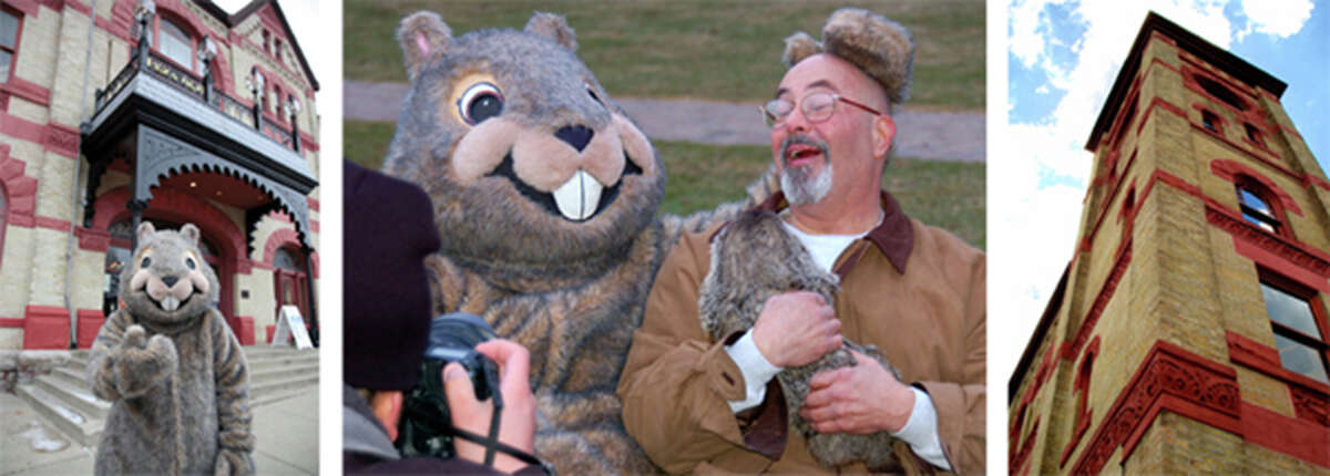 """""""Woodstock Willie"""" poses on the steps of Woodstock Opera House and hams it up with a man holding a real groundhog, while the Opera House towers over Historic Woodstock Square."""