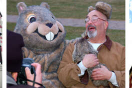 """Woodstock Willie"" poses on the steps of Woodstock Opera House and hams it up with a man holding a real groundhog, while the Opera House towers over Historic Woodstock Square."