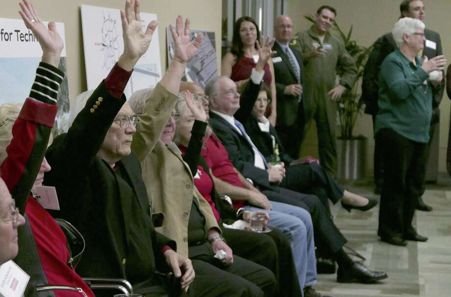 People who once worked at Kelly AFB raise their hands to be recognized during the anniversary celebration. Photo: Billy Calzada / / San Antonio Express-News