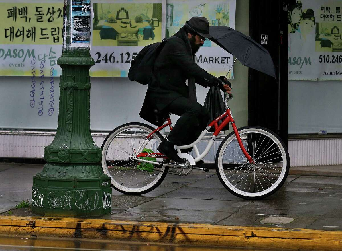 A man rides a bicycle while holding an umbrella during a rain storm Wednesday, Jan. 18, 2017, in Oakland, Calif. The San Francisco Bay Area is being hit with a new series of rain storms.