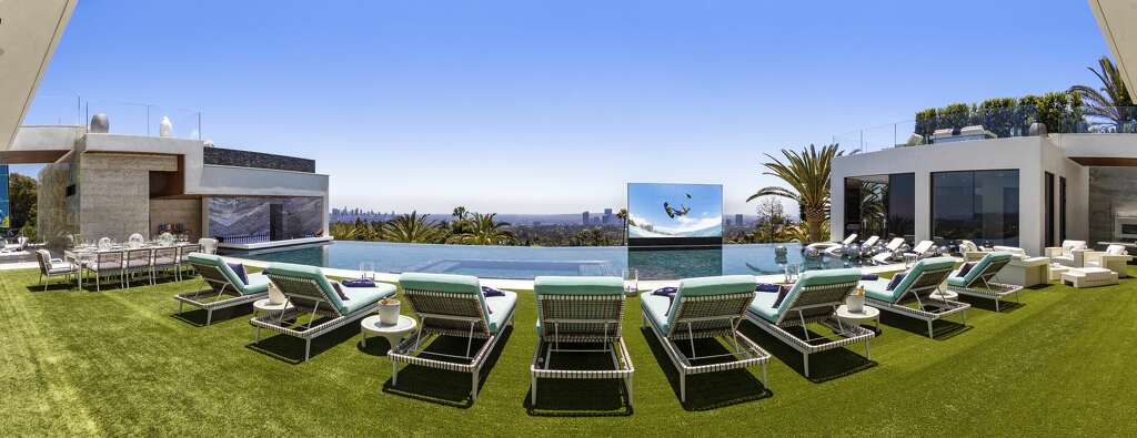 Lounging area next to the 85-foot glass tile infinity swimming pool with a swim-up bar and pop-up TV screen Photo: Photos Courtesy Of Berlyn Photography