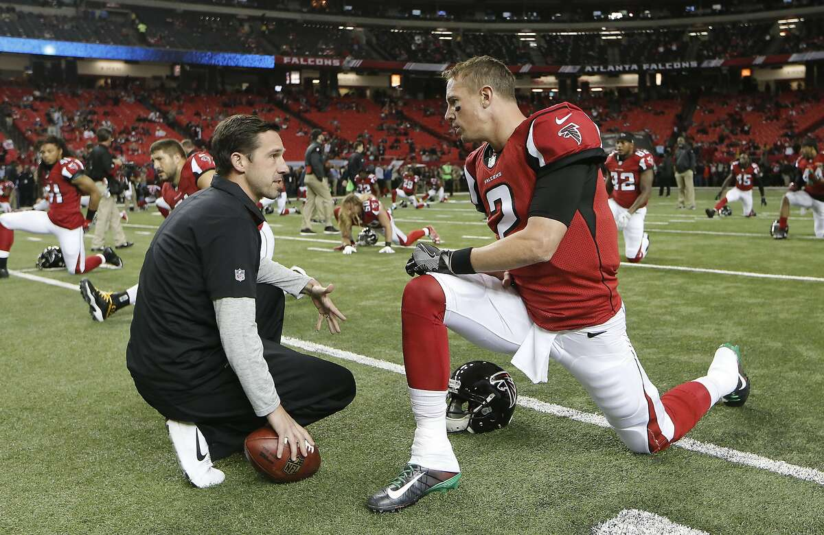 FILE - In this Dec. 4, 2016, file photo, Atlanta Falcons quarterback Matt Ryan (2) speaks with offensive coordinator Kyle Shanahan before the start of an NFL football game against the Kansas City Chiefs, in Atlanta. Might be hard to believe, but it wasn't all that long ago that the shotgun formation was something of a curiosity in the NFL, used less than once every five plays in 2006.(AP Photo/John Bazemore)