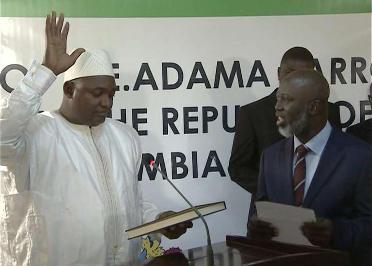 Adama Barrow, left, is sworn in as President of Gambia at Gambia's embassy in Dakar Senegal in this image taken from TV Thursday, Jan 19, 2017. A new Gambian president has been sworn into office in neighboring Senegal, while Gambia's defeated longtime ruler refuses to step down from power, deepening a political crisis in the tiny West African country. (RTS via AP)