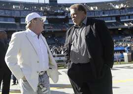 Oakland Raiders owner Mark Davis, left, talks with general manager Reggie McKenzie, right, before an NFL football game between the Oakland Raiders and the Indianapolis Colts in Oakland, Calif., Saturday, Dec. 24, 2016. (AP Photo/Marcio Jose Sanchez)