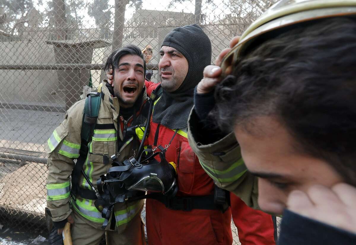 TOPSHOT - A firefighter consoles his comrade after the collapse of Iran's oldest high-rise, the 15-storey Plasco building in downtown Tehran on January 19, 2017. / AFP PHOTO / STRSTR/AFP/Getty Images