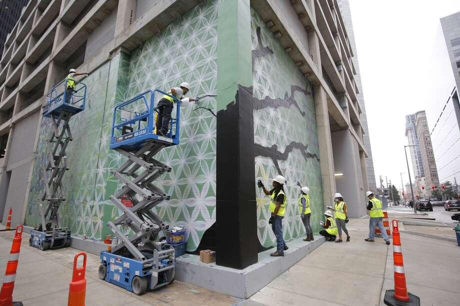 "Public artist Reginald Adams and his crew work on the ""Tree of Life"" mural at the corner of Rusk and Travis, the site of Skanska's Capitol Tower development. Photos provided by Skanska. Photo: Craig Hartley / Courtesy Of Skanska"