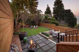 The landscaped backyard includes a mature shade tree  and level lawn.