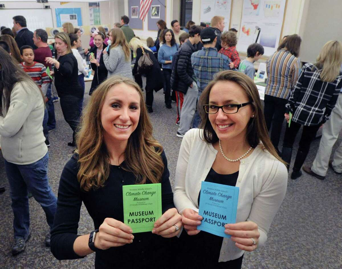 Western Middle School teachers Tyler Mecozzi, left, and Michele Giorlando DeRosa, hold passports for the opening night for the Climate Change Museum produced by the 7th Grade STEMinar class at Western Middle School in Greenwich, Conn., Wednesday, Jan. 18, 2017. Mecozzi, a science teacher at the school and Giorlando DeRosa, an English teacher at the school, were the faculty advisors for the museum.