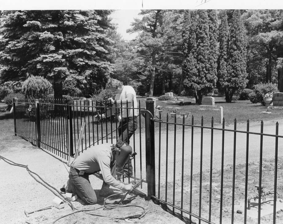 Jeff Snelenberger, welding, and Tab Maki put up gates at the two main entrances to Midland Municipal Cemetery on Orchard. After the public gets used to the gates, they will be closed at night. Chains will be placed across other entrances. June 1985 Photo: Daily News File Photo