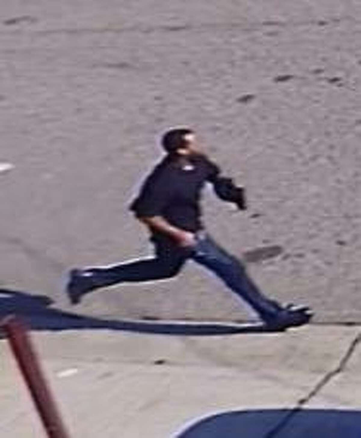 A man holding what appears to be a gun after a homicide in Oakland, officials said. Oakland police are searching for the suspect.